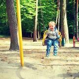 获得愉快的矮小的白肤金发的男孩在摇摆的乐趣 免版税库存图片