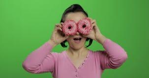 获得愉快的美丽的少女摆在和与油炸圈饼的乐趣 o 股票视频