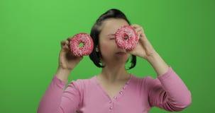 获得愉快的美丽的少女摆在和与油炸圈饼的乐趣 o 股票录像