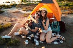 获得愉快的年轻的夫妇野营由湖的乐趣 免版税库存图片