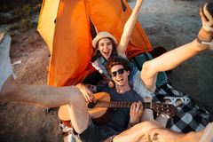 获得愉快的年轻的夫妇野营由湖的乐趣 免版税库存照片