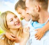 获得愉快的年轻的家庭乐趣户外 免版税库存照片
