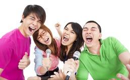 唱歌与卡拉OK演唱的年轻小组 免版税库存照片