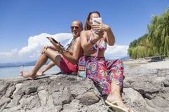 获得成熟的夫妇观看膝上型计算机的乐趣 免版税图库摄影