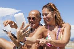 获得成熟的夫妇观看膝上型计算机的乐趣 免版税库存照片