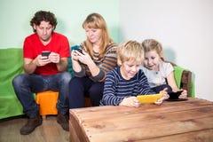获得所有的家庭与比赛的乐趣在智能手机 免版税图库摄影