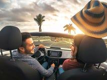 获得时髦富有的夫妇驾驶敞篷车汽车在日落-愉快的浪漫恋人的乐趣享受他们的在敞蓬车汽车的旅行 免版税库存照片