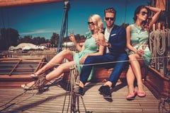 获得时髦的富裕的朋友在豪华游艇的乐趣 免版税库存图片