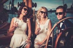 获得时髦的朋友在游艇的乐趣 免版税库存图片