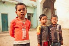 获得未认出的可怜的孩子在印地安镇农村街道上的乐趣  图库摄影
