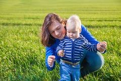 年轻获得母亲和她的儿子乐趣,使用在绿色领域 库存照片