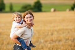 年轻获得母亲和她的小的儿子在黄色干草领域的乐趣 库存图片