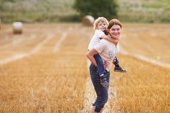 年轻获得母亲和她的小的儿子在黄色干草领域的乐趣 库存照片