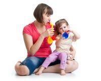 获得母亲和孩子的女孩与音乐玩具的乐趣 库存图片