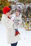 获得母亲和小孩的男孩与雪的乐趣在冬日 免版税库存图片