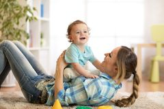 获得母亲和小的儿子在地板上的一个乐趣在家 一起放松的妇女和的孩子 免版税图库摄影