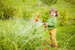 获得母亲小的帮手浇灌庭院和乐趣 免版税库存图片