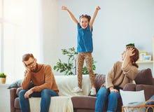 获得淘气,恶作剧,儿童的女孩跳,笑和乐趣,父母强调说与头疼 免版税库存图片