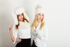 获得温暖的冬天的衣物的两个女孩乐趣 库存照片