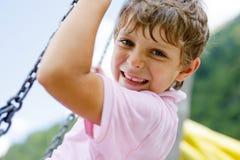 获得滑稽的孩子的男孩与用水时在室外操场,当是湿的飞溅的链摇摆的乐趣 库存图片
