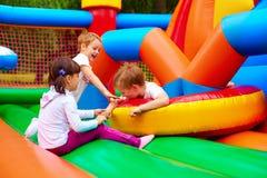 获得激动的孩子在可膨胀的吸引力操场的乐趣 免版税图库摄影