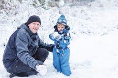 获得父亲和小孩的男孩与雪的乐趣在冬日 库存图片