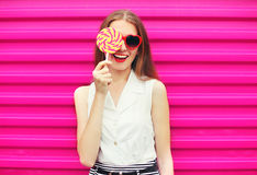 获得甜点相当的少妇与棒棒糖的乐趣在桃红色 免版税图库摄影