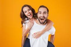 获得白种人的夫妇的图象乐趣,当扛在肩上快乐的妇女的人,被隔绝在黄色背景时 免版税库存照片