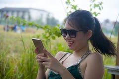 获得的乐趣年轻愉快的亚裔中国妇女使用坐的手机的互联网户外 免版税库存图片