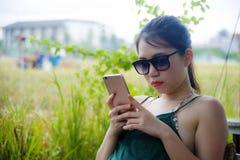 获得的乐趣年轻愉快的亚裔中国妇女使用坐的手机的互联网户外 库存图片