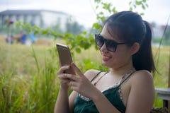 获得的乐趣年轻愉快的亚裔中国妇女使用坐的手机的互联网户外 免版税库存照片