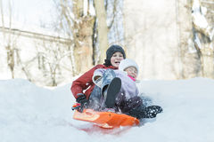 获得的兄弟姐妹在冬天塑料雪滑子的下坡乐趣户外 免版税库存照片
