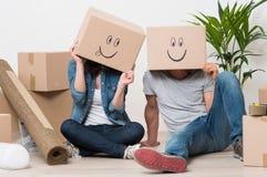 获得的夫妇乐趣,当移动在家时 图库摄影