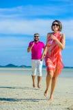 获得的夫妇在海滩的乐趣 白色T恤杉、白色长裤和太阳镜 白色比基尼泳装,赤足在白色沙子 图库摄影