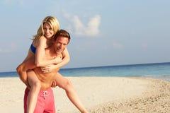 获得的夫妇热带海滩假日的乐趣 免版税库存照片