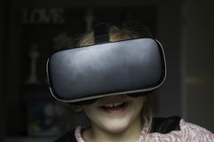 获得的女孩乐趣在家与VR耳机 库存图片