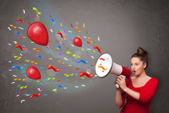 获得的女孩乐趣,呼喊入有气球的扩音机 免版税库存图片