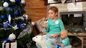 获得的女孩吃圣诞节曲奇饼,与玩具的儿童游戏和吃蛋糕macaron的乐趣,在壁炉附近和 股票视频