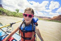 获得的女孩在一次河漂流旅行的乐趣在科罗拉多河下 免版税库存照片