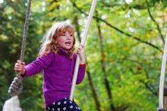 获得的女孩在树绳索摇摆的乐趣 库存图片