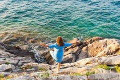获得的女孩站立在岩石的乐趣在海附近 库存照片