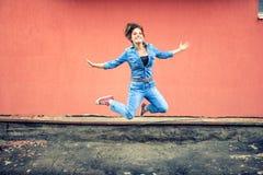 获得的女孩跳和乐趣 牛仔裤和都市成套装备的,微笑的行家女运动员跳跃和 图库摄影