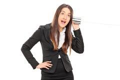 获得的女实业家与锡罐电话的乐趣 免版税库存照片