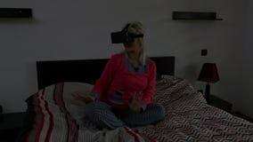 获得的妇女坐她的床和乐趣,当佩带虚拟现实耳机- VR时 影视素材