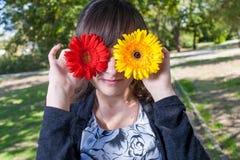 获得的妇女掩藏她俏丽的眼睛的乐趣由两朵花 图库摄影