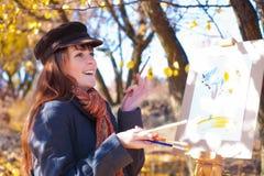 获得的妇女笑在画架附近的乐趣 免版税库存照片