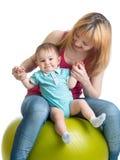 获得的妈妈和的婴孩在体操球的乐趣 免版税图库摄影