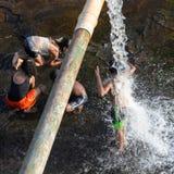 获得的孩子乐趣用落从管子的水 图库摄影