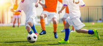 获得的孩子打足球赛的乐趣 青年孩子的足球比赛 在学校沥青的室外橄榄球比赛 年轻Footballlers 免版税库存图片