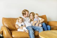 获得的家庭在沙发的乐趣 图库摄影